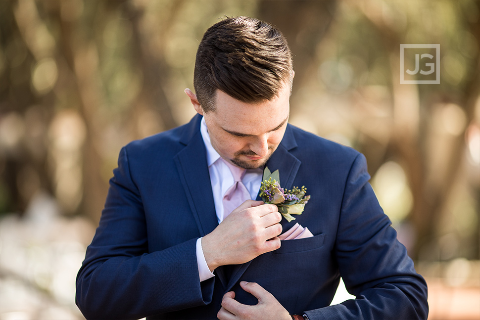 Groom adjusting his boutonnière