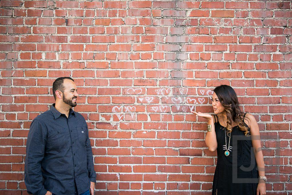 downtown Laguna Beach engagement photo brick wall